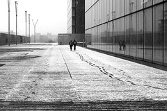 Along the wall of mirrors (pascalcolin1) Tags: paris13 bnf homme man woman femme couple reflets reflection miroir mirrors neige snow mur wall photoderue streetview urbanarte noiretblanc blackandwhite photopascalcolin 50mm canon50mm canon