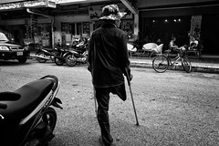 Still 6 millions land mines in Cambodia today. 110 millions in the world. (rvjak) Tags: cambodge kompot cambodia southeast asia asie du sud est d750 nikon noir blanc black white bicycle street rue mine landmine handicapé jambe béquille crutch hat chapeau