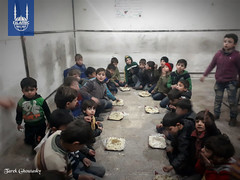 Young children eating on the ground in Syria. Because of the siege, food is scarce in the area.