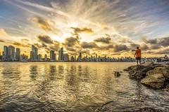 Sunset with fisherman (rqserra) Tags: entardecer pordosol praia sol nuvens pedras pescador reflexos sunset prédios beach sun clouds rocks fisherman reflexes dourado golden rqserra brazil