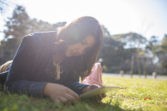 High-teen woman using digital tablet in public park (Apricot Cafe) Tags: img30062 asia asianandindianethnicities healthylifestyle japan japaneseethnicity kyotocity kyotoprefecture sigma35mmf14dghsmart backlit casualclothing charming cheerful citylife day digitaltablet enjoyment expectation freedom greencolor happiness hopeconcept kyotogyoen lawn lensflare lifestyles lyingonfront nature oneperson onlywomen outdoors photography portrait publicpark reading relaxation smiling springtime sunlight sustainablelifestyle teenager waistup walking weekendactivities women youngadult