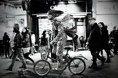 IMG_1313 (JetBlakInk) Tags: composition mono streetscene streetphotography streetartist art statue livestatue bicycle crowds chinatown subjecttoground people cyclist