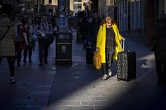 Arrivals (Leanne Boulton) Tags: people urban street candid portrait streetphotography candidstreetphotography streetlife woman female face expression walking motion travelling travel suitcase bright yellow coat style fashion downhill tone texture detail depth naturallight outdoor sunlight light shade shadow shadows sunshine city scene human life living humanity society culture canon canon5d 5dmarkiii 70mm ef2470mmf28liiusm color colour glasgow scotland uk leadinglines spotlight redhead ginger black contrast