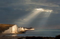 Spotlight on the Sisters (adrians_art) Tags: sevensisters sevensistersnationalpark englishchannel england chalkcliffs hills eastsussex eastbourne sea water coast shore waves tide lightbeams light dark rays sky clouds silhouettes sgadows