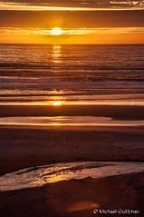 A Sunset Along the Oregon Coast (Michael Guttman) Tags: oregoncoast newport oregon coast beach sunset ocean sea waves water sun sunsetcolors sand reflections layers lines clouds sky nikon d90
