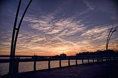 Sunset from the Pier (Gerry Lewicki) Tags: burlington ontario pier park lake water sunset sky clouds building lights railing bench