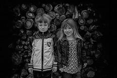 Kids near woodpile (jauza1) Tags: bw blackandwhite noireblanc portrait person people kids child children enfant girl fille boy garcon little young
