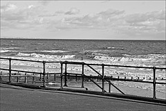 Hornsea sea front Black and White (brianarchie65) Tags: bridlington flamboroughhead blackandwhitephotos blackandwhitephoto unlimitedphotos hornsea railings path beach waves sea warningsign clouds sky canoneos600d geotagged brianarchie65 ships ngc