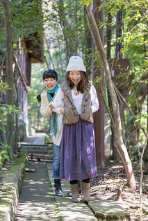 Happy Japanese sisters hiking in forest