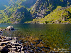 Gin-Clear Waters (liamearth) Tags: earth shore sky mountain sceneic wilderness beautiful sea view outdoor water western landscape wild lofoten norway arctic circle traveling real life camping serene mountainside still clear texture contrast ocean cliff bay beach colour vestvågøya rock grass green pastures field ballstad leknes lågvatnet skottinden