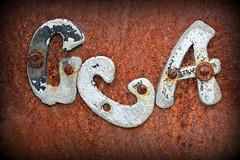 Sleeping on the Job (Doris Burfind) Tags: rust metal letters junk junkyard weathered decay sign