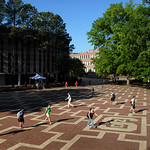 Students head to and from class near the brickyard on a sunny Spring day.
