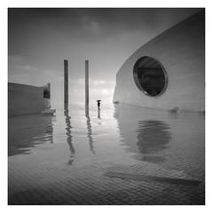 Rain Walker (Vesa Pihanurmi) Tags: portugal lisbon champalimaudfoundation champalimaudcenter man rain character figure reflection wet architecture umbrella streetphotography monochrome