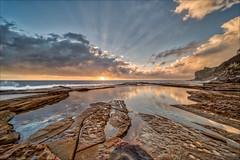 Action behind the clouds (JustAddVignette) Tags: australia clouds cloudysunrise dawn deewhy landscapes newsouthwales northernbeaches ocean reflections rocks seascape seawater sky sun sunrays sunrise sydney water