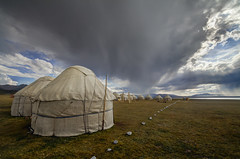 Yurt Camp at Lake Song Kul (Joost10000) Tags: landschaft grass landscape sky field yurt mountains highlands rain clouds kyrgyzstan asia canon canon5d outdoors travel adventure centralasia village wild wilderness cold steppe songkul sonkul lake water camp
