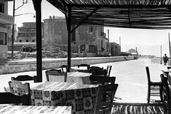 Taverna Lunch (tobysx70) Tags: nikon f2 photomic slr camera kodak trix pan 35mm 135 bw black white film tx iso 400 rollfilmweek january 2018 taverna lunch heraklion crete greece greek restaurant tables chairs shadows woman pedestrian car vanishing point day1 toby hancock photography