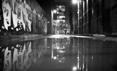 Wet Night (4foot2) Tags: streetphoto streetshot street streetphotography nightphotography night afterdark dark puddle water reflection manchester graffiti graff streetart monochrome mono m3 lights manchestergraffiti manchestergraff analogue film filmphotography 35mmfilm 35mm 35mmf2 35mmf2summicron summicron leica leicam3 bw blackandwhite rangefinder rolleiretro rolleiretro400s 400s kodak hc110 kodakhc110 4foot2 4foot2flickr 4foot2photostream fourfoottwo 2018