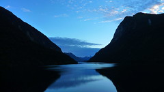 Doubtful Sound Hitting the Twilight Zone (Eye of Brice Retailleau) Tags: angle beauty composition landscape nature outdoor panorama paysage perspective scenery scenic view extérieur ciel sky backpacking earth mountain mountains travel vista reflection reflet mirror colourful colours clouds light blue water waterscape eau montagne calme new zealand doubtful sound fjord hour twilight dark