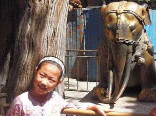 China (Beijing, Forbidden City) A beautiful chinese girl posing with lovely elephant in the Emporer Garden