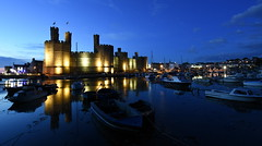 Cearnarfon Knights (Peter.S.Roberts) Tags: caernarfoncastle caernarfon northwales castle night evening longexposure blue bluehour dusk illuminations light lighting boats river moat harbour harbor reflections dark lights colors colours water sea seiont riverseiont town village shadows buildings homes houses township nightfall historic historicsite cadw historical stone masonry menaistrait coast coastal tidal summer warm hills sky clouds quiet calm relaxing serene peaceful tranquil