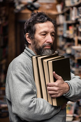 Portrait of authentic senior man on book market (antelhawi) Tags: portrait old man beard mustache senior library book market bibliophile sad good eyes face looking view sadness expression emotion realpeople read wisdom librarian handsome elderly age writer author public scientist bookshelves mature people literature retirement caucasian background hobby