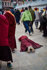 Tibetan pilgrim making full body prosternation while makin the Kora around Boudhanath Stupa, Kathmandu, Nepal (Alex_Saurel) Tags: pélerinage asie prostrating culture fullbodyprostration 35mmprint pilgrimage scans tibetanprosternation moine laying monk prostration སྐོར་ར kora asian kasaya tibetanmonk pattern motif circumambulation action moinetibétain bouddhisme tibetanpeople group buddhism people khāsacaitya boudhanath kesa asia streetscene khāsti basket travel sanctuairebouddhiste lifescene बौद्धनाथ imagetype buddhistsanctuary photospecs photoreport jarungkhashor photoreportage reportage kathmandu bouddhanath bodnath byarungkhashor photojournalism stockcategories religion day traditional time katmandou tradition nepal scènedevie lifestyles sony50mmf14sal50f14