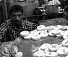 Looking askance at a customer (magiceye) Tags: sweet seller mdaliroad mumbai streetfood street streetphoto india monochrome blackandwhite streetportrait