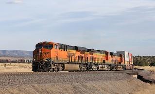 A long BNSF S-LPCLHA2-07 stack train grinds upgrade between Pica & Yampai, Az.