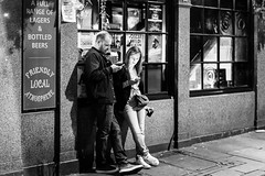 Modern Dating (Sean Batten) Tags: london england unitedkingdom gb soho blackandwhite bw streetphotography street nikon df 58mm city urban people drinking pub couple candid valentinesday signs window