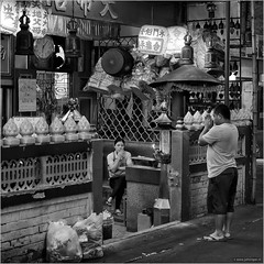 Ora et labora (John Riper - AWAY FOR AWHILE) Tags: johnriper street photography straatfotografie square vierkant bw black white zwartwit mono monochrome bangkok thailand candid john riper xt2 fujifilm xf35 f2 adoration sitting working temple man woman eye contact night clock chinese