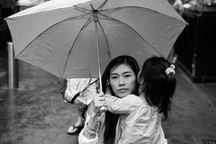 Hold On (McLovin 2.0) Tags: mother street umbrella streetphotography streetphoto urban city rain sydney sony a7s 55mm zeiss bw monochrome people family eyes