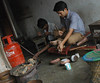 Two young Nepalese men custom making Tibet Buddhist ritual implements from copper, forge, petroleum, cup, stools, carpets, room, concrete floor, Boudha, Kathmandu, Nepal (Wonderlane) Tags: twoyoungnepalesemencustommakingtibetbuddhistritualimplementsfromcopper forge petroleum cup stools carpets room boudha kathmandu nepal two young nepalese men custom making tibet buddhist ritual implements from copper concretefloor fabrication fabricating