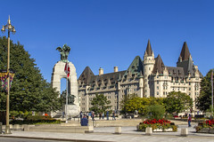 Ottawa's Confederation Square (Kev Gregory (General)) Tags: confederation square ottawa national war memorial fairmont château laurier providing backdrop capital city ontario canada red white flag building gothic grand park flowers trees colour colourful arch road lamp lampposts blue clear sky summer warm tourists tourism verdigris roof bushes idyllic beautiful concrete pavement quite rest architecture clean impressive proud heritage tidy safe kev gregory canon 7d