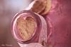 Bottled love... (Maria Godfrida) Tags: bottle macromondays inabottle pink macro heart love bottled ribbon soft light sidelit wood textures heartshaped 7dwf crazytuesdaytheme hearts