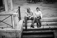 Flirt (Tom Levold (www.levold.de/photosphere)) Tags: venice xpro2 street venedig fuji xf56mm venezia people candid portrait porträt bw sw couple man smoking jungefrau jungermann young youngwoman paar flirt stairs treppen