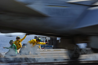 Sailors signal for an F/A-18F Super Hornet to launch from the aircraft carrier.