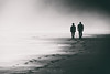 Film Noir (Mimadeo) Tags: couple person two beach blackandwhite black white walking water people walk silhouette sand man summer woman shore together mist misty haze hazy fog foggy footprint footprints toned monochrome