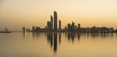 Abu Dhabi Corniche (Sniper Zaytsev) Tags: دولةالإماراتالعربيةالمتحدة أبوظبي emirati emirates skyline cityscape gulf arabian sandstorm shamal yellow sepia 35mm zeiss abu dhabi cornich buildings sony a7r uae marina water reflection sunrise glow desert skyscrapers tall