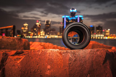 Lens on top of rock with Detroit skyline shoot through (Ncor: Photography) Tags: lens photograph black equipment camera photographic professional digital glass photo aperture hobbies focal studio lense optical focus objective eyesight optic instrument angle technique macro shutter technology sky suburbs blue photography plastic modern dream capture architecture city center industrial semaphore motor panorama american capital vacation industry scenic scene michigan building usa town america street downtown night river travel panoramic skyline traffic urban view business detroit nikon 18 85