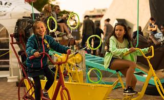 Two girls on soap bubble making bikes.