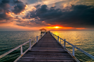 Wooden bridge in the sea at sunset