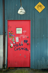 Joan Cusack - 2015 (James_D_Images) Tags: blue corrugated metal building wall sign bicycle slippery lamp drain pipe doorstep rat trap red door tagged tagging graffiti graffito joancusack stickers decals 2015 granvilleisland vancouver britishcolumbia