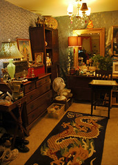 Room interior, Tibetan dragon carpet, art supplies, brushes, table lamp, chest of drawers, mirror, silk wall paper, buddhas, angel, shoes, plant, tables, bookshelf, fan, chair, Dzambhala Thangka, apartment, Greenwood, Seattle, Washington, USA (Wonderlane) Tags: 0029 roominterior tibetandragoncarpet artsupplies brushes tablelamp chestofdrawers mirror silkwallpaper buddhas angel shoes plant tables bookshelf fan chair dzambhalathangka apartment greenwood seattle washington usa