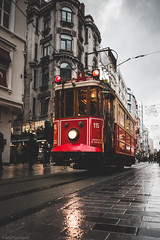 Little Red riding in the Beyoğlu 'hood (The Frustrated Photog (Anthony) ADPphotography) Tags: beyoglu category istanbul places street tram transport travel turkey travelphotography streetphotography rain buildings canon1585mm canon70d canon outdoor train road city reflections tourism