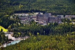 A View to the Banff Springs Hotel While on a Hike to Tunnel Mountain (Banff National Park) (thor_mark ) Tags: nikond800e lookingsw day2 triptoalbertaandbritishcolumbia banffnationalpark capturenx2edited colorefexpro banffspringshotel bowriver river tunnelmountainbanffhiking hiketotunnelmountain tunnelmountaintrail outside nature landscape rockymountains canadianrockies mountainside hillsides trees hillsideoftrees evergreens hotel canadianflag flag flagpole portfolio project365 alberta canada