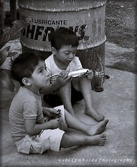 reading (Mexico) (gabi lombardo) Tags: kinder bambini enfants children lettura reading lesen container piedi füsse bidone monochrome schwarzweis bottiglia flasche bottle