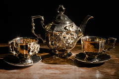 Golden Tea Set (donnicky) Tags: blackbackground closeup cup dishes glare golden indoors light nopeople old oldfashioned publicsec reflections retro shiny stilllife studioshot table teapot vintage wood