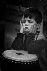 Drumming difficulties (Frank Fullard) Tags: frankfullard fullard candid street portrait monochrome blackandwhite blanc noir music child drum pronlem difficult hard unhappy lol fun sorrow sorry sad forlorn