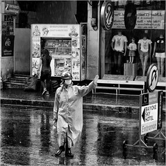Rainy day traffic policeman (John Riper) Tags: johnriper street photography straatfotografie square vierkant bw black white zwartwit mono monochrome bangkok thailand candid john riper xt2 fujifilm rain traffic ward policeman wet pavement window shop question mark sign baiyoke sky hotel raincoat man boutique food court facemask helmet