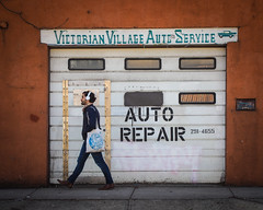 Auto Repair (tim.perdue) Tags: victorian village auto repair service short north arts district columbus ohio downtown urban city man person figure walking candid street sidewalk garage door sign orange wall high st building window mailbox headphones bag olympus omd em10mkii tamron 14150mm mirrorless micro four thirds mft m43 color explore interesting explored popular interestingness